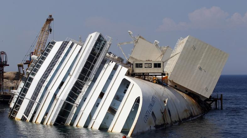 razno 12.09.13. The capsized cruise liner Costa Concordia lies surrounded by cra